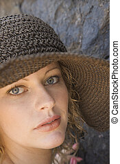 Young woman wearing hat.