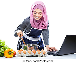 Young woman wearing hijab cooking with reference the laptop...
