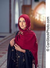 young woman wearing hijab posing at mosque