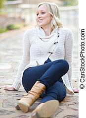 Young woman wearing jeans and knit top sitting on pathway