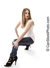 young woman wearing jeans crouching on white background