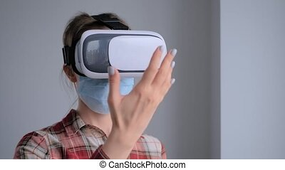Young woman wearing medical face mask and virtual reality ...