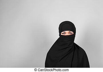 Young woman wearing niqab on background