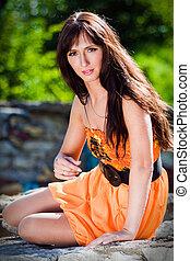 Young woman wearing orange dress
