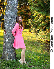 Young woman wearing pink dress, leaning her back to a tree, with sunset light park in background.