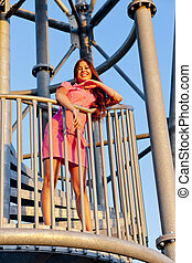 young woman wearing pink dress standing on stairs of lookout tower