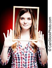 Young woman wearing plaid shirt holding wooden frame