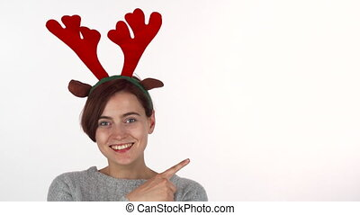 Young woman wearing reindeer antlers headband pointing at the copy space