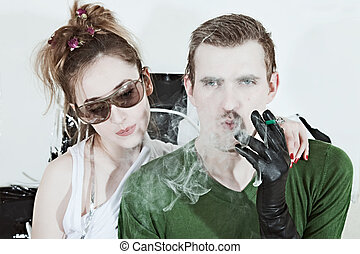 Young woman wearing sunglasses and man with a cigarette
