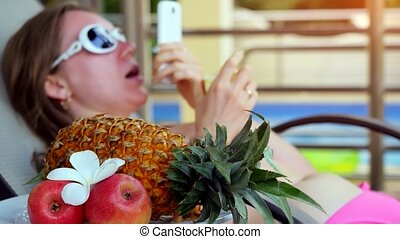 Young woman wearing sunglasses lying on a sunbed talking on smartphone has chatting next to the swimming pool and eats fruits on summer holidays while vacation.