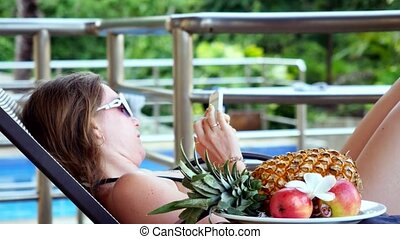 Young woman wearing sunglasses lying on a sunbed talking on smartphone has chatting next to the swimming pool with fruits and flower on the foreground. 3840x2160