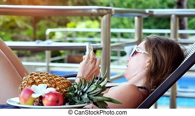 Young woman wearing sunglasses lying on a sunbed talking on smartphone has chatting next to the swimming pool with fruits and flower on the foreground.