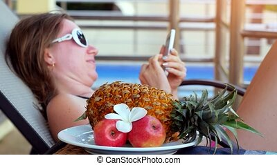 Young woman wearing sunglasses lying on a sunbed uses...