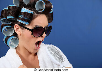 Young woman wearing sunglasses with her hair in rollers