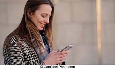 Young woman wearing trendy coat of black and white colors using her smartphone in the street.