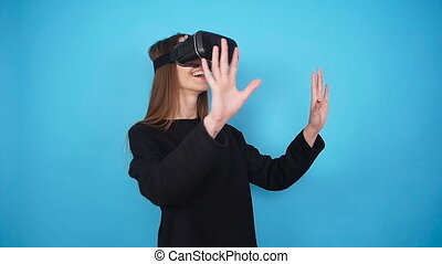 Young woman wearing virtual reality glasses on colorful ...