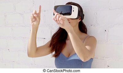 Young woman wearing virtual reality goggles leaning against...