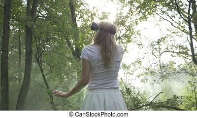 Young woman wearing VR headset in the forest experiencing augmented virtual reality