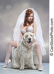 Young woman wearing wedding lingerie with dog