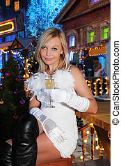 Young woman wearing white dress sits at wooden table with glass of champagne