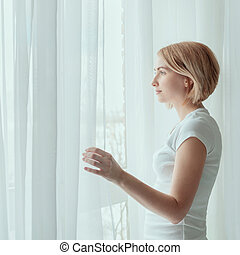 Young woman wearing white t-shirt looking out through window