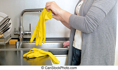Young woman wearing yellow latex gloves before cleaning kitchen