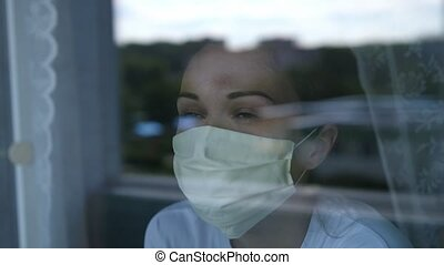 pensive young woman wears a mask to protect herself from covid-19 while looking out the window.