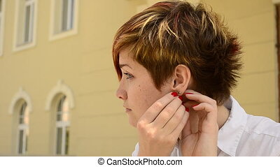 young woman wears earrings and looks in the mirror