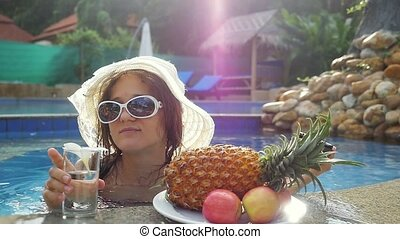 Young woman wears hat and sunglasses drinking water while...