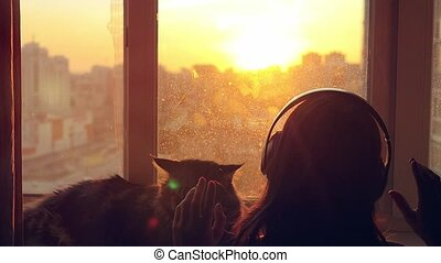 Young woman wears headphones looking on the window and relaxing with her lovely Maine Coon cat at window with blurred city background at sunset in slowmotion