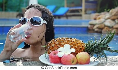 Young woman wears sunglassed drinks water while sunbathing...