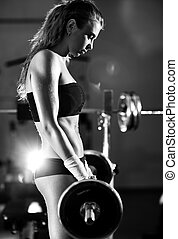 Young woman weight training. Black and white colors.