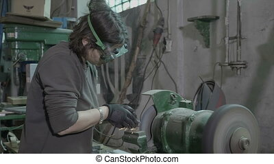 Young woman welder or blacksmith wearing protection...