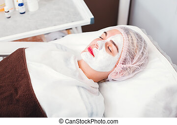 Young woman which applying cosmetic facial mask.
