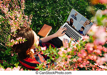 Young woman while working on her laptop on the lawn. Top view, through bush.