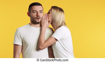 Young woman whispering secrets to surprised man over yellow ...