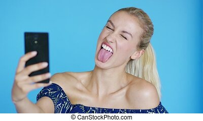 Young woman winking and taking selfie - Beautiful young lady...