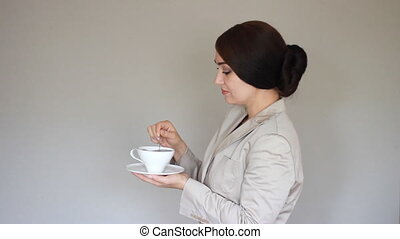 Young woman winks. Businesswoman smiling, looking at camera, holds a cup in his hand and drinking coffee or tea. Break