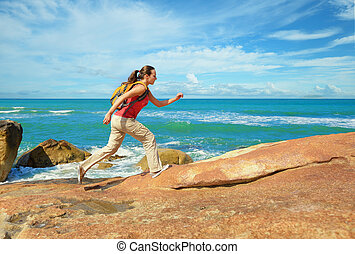 Young woman with a backpack runs on coastal rocks.