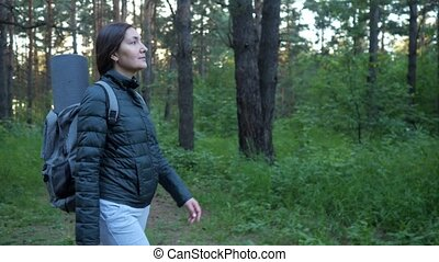 young woman with a backpack walks through the woods alone