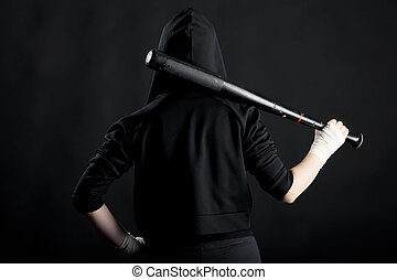 Young woman with a baseball bat. View from the back. hoodlum...