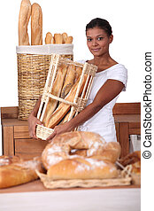Young woman with a basket of baguettes in a baker's shop