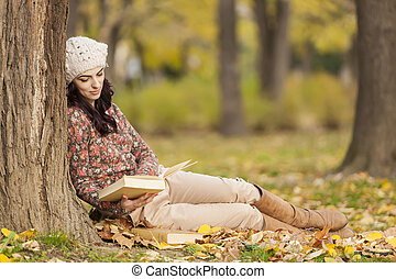 Young woman with a book in the forest