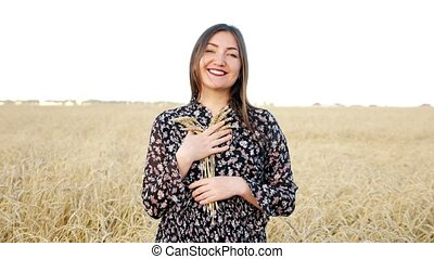 Young woman with a bouquet of ears of ripe wheat in the field