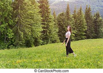 Young woman with a bouquet of flowers walking in a meadow.