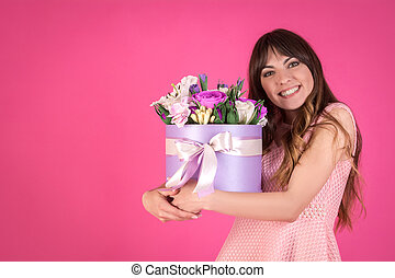 Young woman with a bouquet of peonies on a pink background