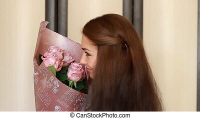 Young woman with a bouquet of roses smiling and sniffing the...