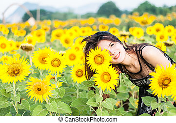 Young woman with a bouquet of sunflowers in the field