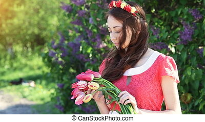 Young woman with a bouquet of tulips at the park in spring