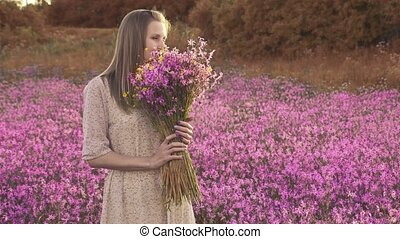 Young woman with a bouquet of wildflowers standing on a ...